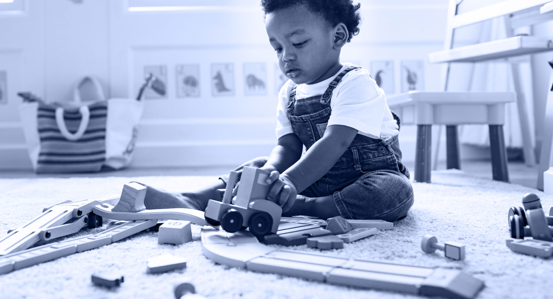 An image of a young toddler boy playing with a wooden train set in a play room for small children